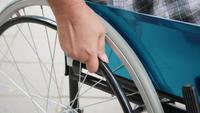Close-up of a patient's hand holding a wheelchair and driving it alone