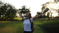 Woman raising her hands happily while walking in nature