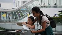 Mamma och dotter tittar på en karta när de reser i staden