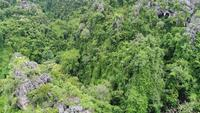 Vista aérea volando sobre un bosque lluvioso de montaña rocosa en Tailandia