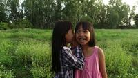 Two little girls whisper telling secrets