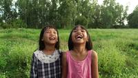Two little girl laughing hearing joke story