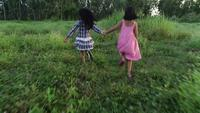 Two little girls running around the park