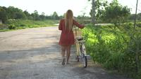 Ung kvinna med cykel som går i parken