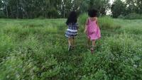 Zwei kleine Mädchen, die um den Park, Freundschaftskonzept laufen