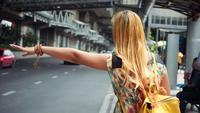 Woman traveler waves down a taxi car in the city