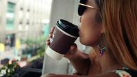 Närbild på en vacker kvinna smaka kaffe nära gatan