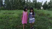 Två små tjejer går genom parken