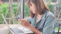 Funcionamento asiático autônomo da mulher do negócio, fazendo projetos no portátil e usando o smartphone ao sentar-se na tabela no café.
