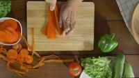 Top view of woman chief making salad healthy food and chopping carrot on cutting board in the kitchen.
