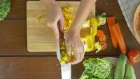 Top view of woman chief making salad healthy food and chopping bell pepper on cutting board in the kitchen.