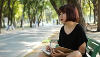 Escritura asiática joven de la mujer del inconformista feliz en su diario en parque.