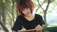 Jeune femme asiatique hipster heureux écrit dans son journal dans le parc.