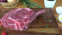 Sluit omhoog van gastronomische chef-kok of kook verse stuk van het delicatessenwinkelstuk van het rundvlees met overzeese zoute en aan de grond gezete kruidige peper.