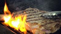 Kochleiter legt ungekochtes Fleischstück auf heißen rauchenden Grill mit Feuer unter Verwendung der Metallzange, Nahaufnahme Zeitlupe