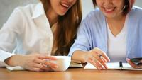 Affärskvinnor använder mobiltelefon och skrivar rapport på träbord. Asiatisk kvinna med telefon och kopp kaffe. Frilansare som arbetar i kafé. Woking utanför kontors livsstil.