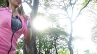 Slow motion - Jonge Aziatische vrouw die op stoep in de ochtend. Jonge sport Aziatische vrouw die in het park loopt. Fitness lopende sportmensen en gezond levensstijlconcept.