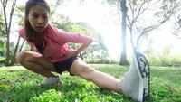 Slow motion - Healthy young asian woman exercising at park. Fit young woman doing training workout in morning. Happy asian woman stretching at park after running workout. Exercise outdoor concept.