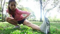 Slow motion - Gezonde jonge Aziatische vrouw oefenen in het park. Fit jonge vrouw training training in de ochtend doen. Gelukkige Aziatische vrouw die zich uitstrekt in het park na het uitvoeren van training. Oefening buiten concept.