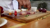 Feche acima do cozinheiro chefe do gourmet ou cozinhe o pedaço fresco do tempero da parte do supermercado fino de carne com sal do mar e pimentas picantes aterradas.