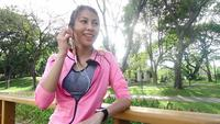 Slow motion - Asian beautiful woman in fitness outfits are using a smartwatch for listen to music, talking on the phone after running in the park. Attractive healthy female jogging.