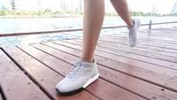 Zeitlupe - junge asiatische Frau, die auf Bürgersteig am Morgen läuft. Asiatische Frau des jungen Sports, die in den Park läuft. Laufende Sportleute der Eignung und gesundes Lebensstilkonzept.