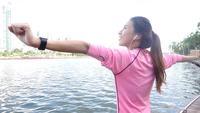 Slow motion - Aziatische mooie vrouw in fitness-outfits zijn met behulp van een smartwatch om naar muziek te luisteren, praten over de telefoon na het lopen in het park. Aantrekkelijke gezonde vrouwelijke joggen.