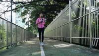 Junge asiatische Frau, die auf Bürgersteig am Morgen läuft. Gesundheitsbewusstes Konzept mit Textfreiraum. Eignungssportleute und gesundes Lebensstilkonzept.