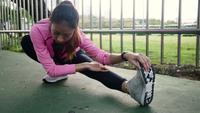 Fitness sport meisje mode sportkleding doen yoga fitness oefening in straat. Fit jonge Aziatische vrouw training training in de ochtend doen. Het jonge gelukkige Aziatische vrouw uitrekken zich bij park na het runnen van training.