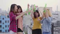 Groep jonge Aziatische vrouwenmensen die en hun wapens omhoog in lucht dansen dansen aan de muziek die door DJ bij zonsondergang stedelijke partij wordt gespeeld op dak. Jonge Aziatische meisjesvrienden die uit met dranken hangen.