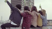 Groupe de jeunes femmes et d'hommes asiatiques dansant et levant les bras en l'air au son de la musique jouée par dj lors d'une soirée urbaine au coucher du soleil sur le toit. Jeunes filles asiatiques et amis garçons sortir avec des boissons