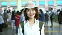 Glückliche asiatische Frau, die den Zug an der Bahnstation auf Reise im Sommer wartet. Thailand Reisekonzept.