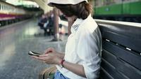 Traveler backpacker Asian woman travel in Bangkok, Thailand. Happy young female sitting on bench using smartphone for talking, reading and texting at train station.