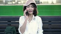 Reisenderwanderer Asiatinreise in Bangkok, Thailand. Glückliche junge Frau, die auf Bank unter Verwendung des Smartphone für das Sprechen, Lesen und Simsen an der Bahnstation sitzt.