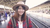 Zeitlupe - glückliche Asiatin, die den Zug an der Bahnstation auf Reise im Sommer wartet. Thailand Reisekonzept.