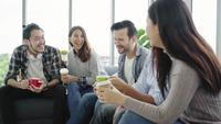Diversité de l'équipe de groupe de jeunes gens tenant des tasses à café et discuter de quelque chose avec le sourire tout en restant assis sur le canapé au bureau Pause café au bureau de création.