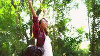 Glücklicher junger Asiatinreisender mit Rucksack gehend in Wald. Wanderer-Asiatin mit Rucksack gehend auf Weg im Sommerwald. Abenteuer-Wandererreisekonzept.