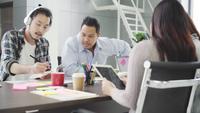 Gruppe zufällig gekleidete Wirtschaftler, die Ideen im Büro besprechen. Am Besprechungstisch versammelten sich kreative Fachleute, um die wichtigen Fragen des neuen erfolgreichen Startprojekts zu diskutieren.