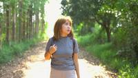 Happy young Asian woman traveler with backpack walking in forest. Hiker Asian woman with backpack walking on path in summer forest. Adventure backpacker travel people concept.