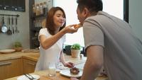Beautiful happy asian couple are feeding each other. Man and woman cooking food in the kitchen. Young asian couple have romantic time while staying at home.
