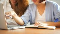 Twee jonge bedrijfsvrouwen die bij lijst in koffie zitten. Aziatische vrouwen met behulp van laptop en kopje koffie. Freelancer die in koffiewinkel werken. Werken buiten de kantoorlevensstijl. Een-op-een vergadering.