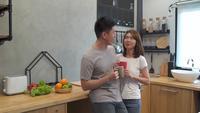 Schöne glückliche asiatische Paare trinken einen Tasse Kaffee zusammen in der Küche. Mann und Frau reden beim Frühstücken. Junge asiatische Paare haben romantische Zeit beim zu Hause bleiben.