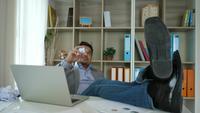 Jeune homme fatigué et paresseux assis au bureau