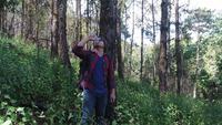 Junger Mann, der Trinkwasser im tropischen Dschungel mit Rucksack wandert.