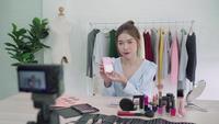 La blogger de belleza presenta cosméticos de belleza que se sientan en la cámara frontal para grabar video. Hermosa pincel de uso de mujer asiática mientras que la revisión compone un video de transmisión en vivo a una red social por Internet.