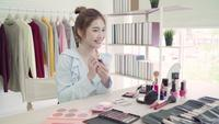 La blogger de belleza presenta cosméticos de belleza que se sientan en la cámara frontal para grabar video. Hermosa mujer asiática usa cosméticos mientras que la revisión compone un tutorial transmitido en vivo a una red social por Internet.