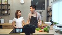 Young asian couple man and woman in kitchen recording video on camera.