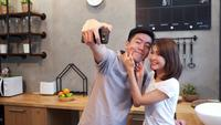 Happy young Asian couple using smartphone for selfie while cooking in the kitchen at home.