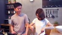 La mujer asiática prepara la comida de la ensalada en la cocina. Los pares asiáticos felices hermosos están cocinando en la cocina.