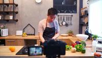 Young asian man in kitchen recording video on camera. Smiling asian man working on food blogger concept with fruits and vegetables in kitchen.